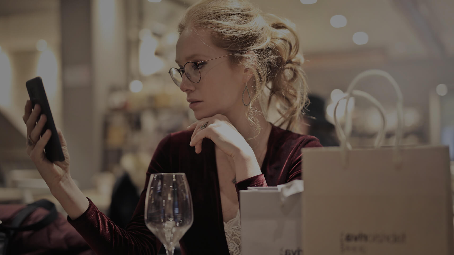 Woman looking at phone in restaurant